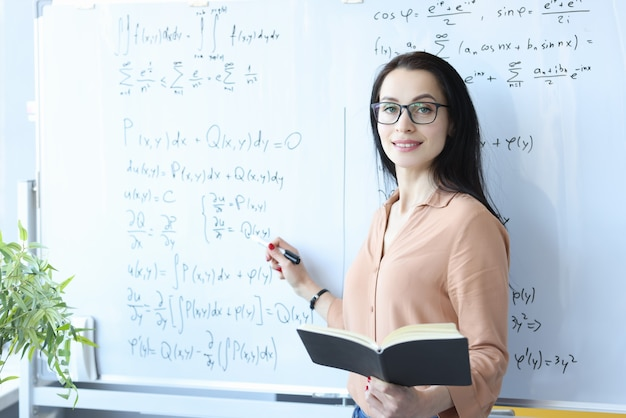 Young woman teacher stands at white board