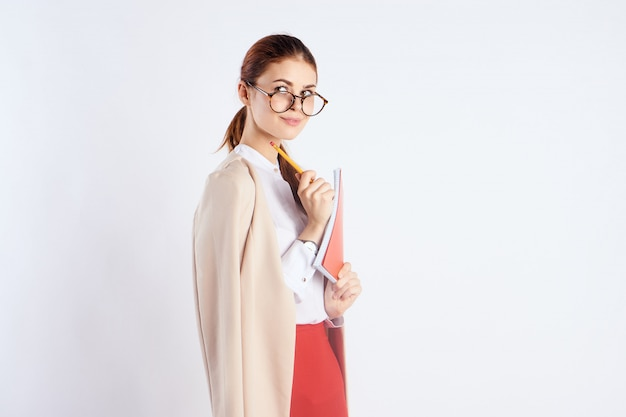 Young woman teacher student businesswoman with folder in hands in studio