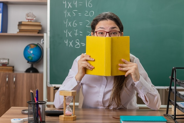 Молодая женщина-учитель в очках держит книгу, закрывающую лицо, готовится к уроку, сидя за школьной партой перед доской в классе