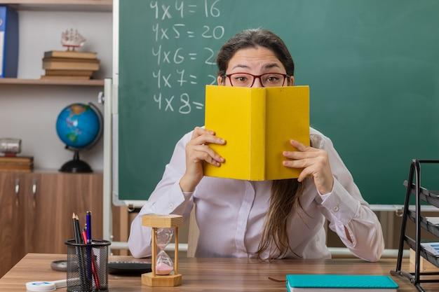 Insegnante di giovane donna con gli occhiali in possesso di libro che copre il viso con esso la preparazione per la lezione seduto al banco di scuola davanti alla lavagna in aula
