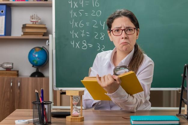 Insegnante di giovane donna con gli occhiali in possesso di libro guardando le pagine attraverso l'ingrandimento confuso seduto al banco di scuola davanti alla lavagna in aula