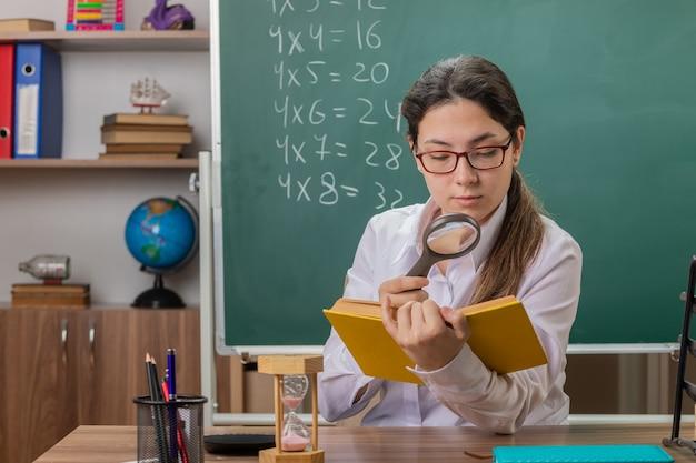 Insegnante di giovane donna con gli occhiali in possesso di libro guardando le pagine attraverso la lente di ingrandimento