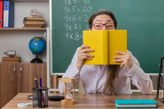 Insegnante di giovane donna con gli occhiali tenendo il libro in preparazione per la lezione di essere confuso e preoccupato seduto al banco di scuola davanti alla lavagna in aula