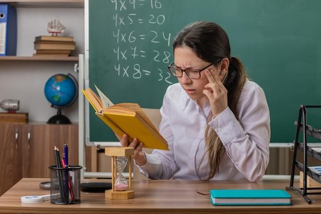 Insegnante della giovane donna con gli occhiali che tengono libro che prepara per la lettura di lezione che è confuso