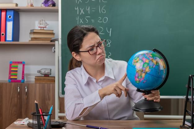 Молодая женщина-учитель в очках держит глобус