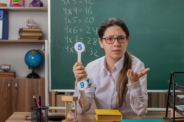 Insegnante di giovane donna con gli occhiali tenendo le targhe che spiega la lezione cercando confuso con il braccio fuori come chiedere seduto al banco di scuola davanti alla lavagna in aula