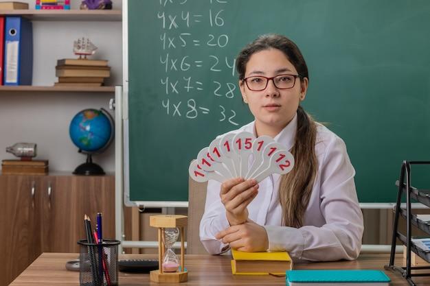 Giovane donna insegnante con gli occhiali tenendo le targhe cercando fiducioso preparando per la lezione seduto al banco di scuola davanti alla lavagna in aula