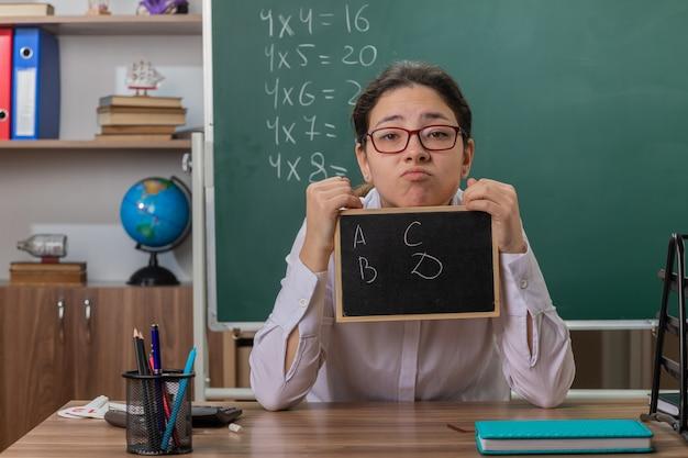Молодая женщина-учитель в очках держит небольшую доску, глядя вперед с смущенным выражением лица, объясняя урок, сидя за школьной партой перед доской в классе