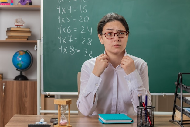 교실에서 칠판 앞에 학교 책상에 앉아 수업을 설명하려고 자신감 식으로 정면을보고 안경을 착용하는 젊은 여자 교사