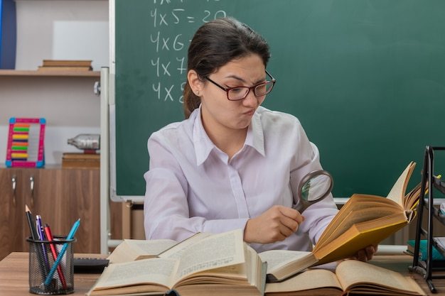 Insegnante di giovane donna con gli occhiali guardando il libro attraverso la lente di ingrandimento essendo confuso e dispiaciuto seduto al banco di scuola davanti alla lavagna in aula