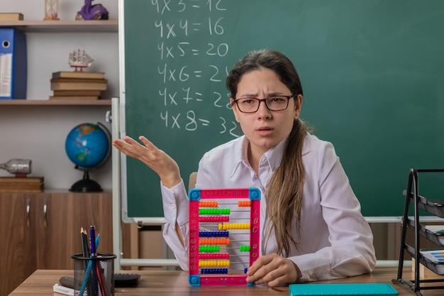 Insegnante di giovane donna con gli occhiali guardando confuso seduto al banco di scuola con le bollette preparazione lezione davanti alla lavagna in aula