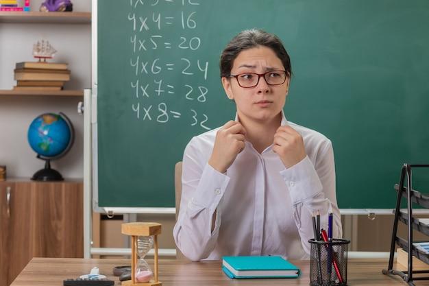 Insegnante di giovane donna con gli occhiali guardando davanti con espressione fiduciosa andando a spiegare la lezione seduto al banco di scuola davanti alla lavagna in aula