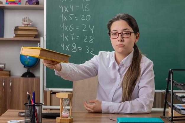 Insegnante di giovane donna con gli occhiali che offre libro guardando fiducioso seduto al banco di scuola davanti alla lavagna in aula