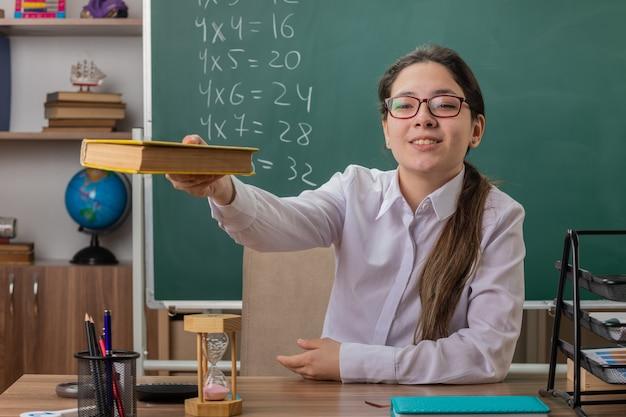 教室の黒板の前に学校の机に座って自信を持って笑顔の本を提供する眼鏡をかけている若い女性教師