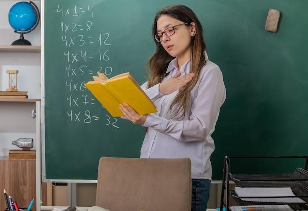 Giovane donna insegnante con gli occhiali libro da lettura che spiega lezione tenendo la mano sul petto guardando fiducioso in piedi al banco di scuola davanti alla lavagna in aula