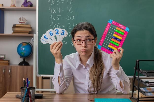 Молодая учительница в очках сидит за школьной партой со счетами и номерными знаками, выглядит усталой и скучающей, дует щеки, объясняя урок перед доской в классе