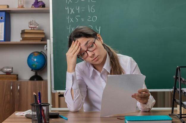 Молодая женщина-учитель в очках сидит за школьной партой с пустыми страницами, проверяет домашнюю работу, выглядит усталой и перегруженной перед доской в классе