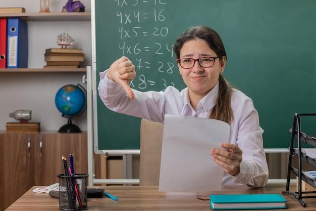 교실에서 칠판 앞에 집에 일을 확인 아래로 엄지 손가락을 보여주는 혼란과 불쾌한 찾고 빈 페이지와 학교 책상에 앉아 안경을 착용하는 젊은 여자 교사