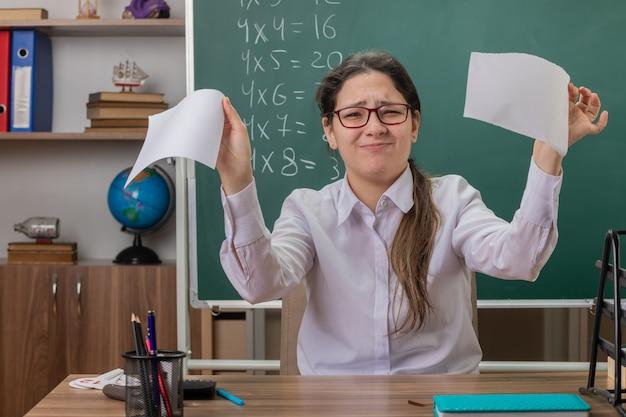 Молодая женщина-учитель в очках разрывает лист бумаги с недовольным видом, сидя за школьной партой перед доской в классе
