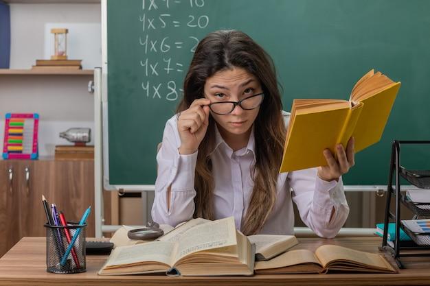 Insegnante di giovane donna con gli occhiali con il libro è concentrato seduto al banco di scuola davanti alla lavagna in aula