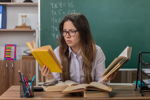 Молодая женщина-учитель в очках с книгами выглядит смущенной и очень взволнованной, сидя за школьной партой перед доской в классе