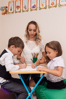 Young woman teaches children to draw