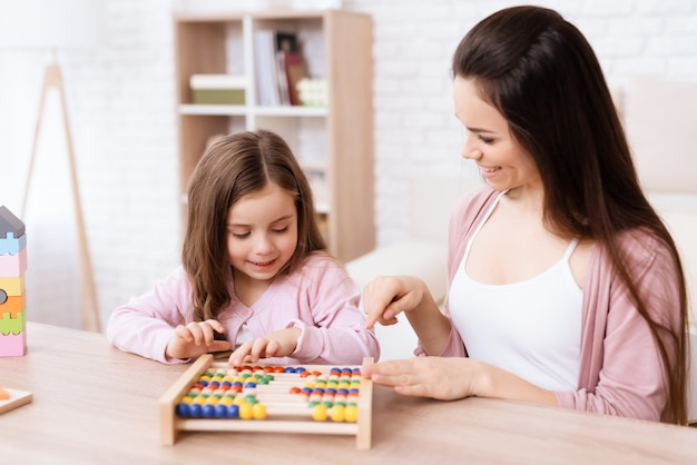 Young woman teaches a little girl math on wooden abacus.