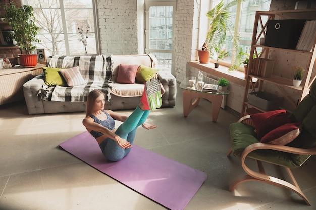 検疫しながら、フィットネス、有酸素、スポーティなライフスタイルのオンラインコースを自宅で教えている若い女性。孤立した状態でアクティブになる、ウェルネス、動きのコンセプト。下半身、有酸素運動のトレーニング。