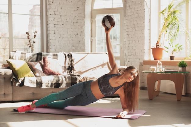 Молодая женщина преподает дома онлайн-курсы фитнес-аэробного спортивного образа жизни во время карантина