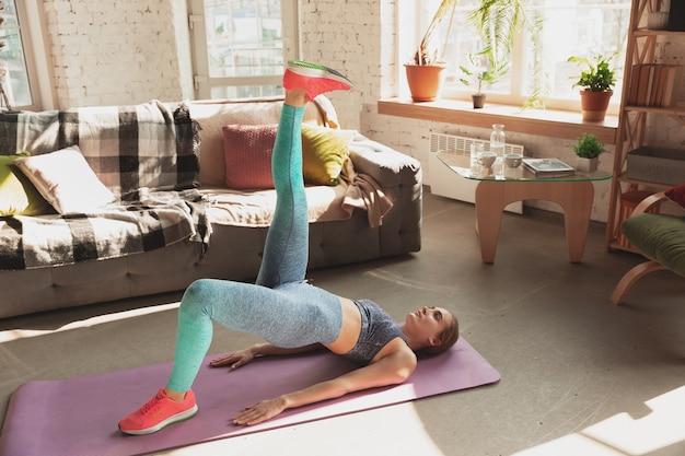 検疫中に自宅でフィットネス、エアロビクス、スポーティなライフスタイルのオンラインコースを教える若い女性。孤立しながらアクティブになる、健康、運動のコンセプト。ストレッチ、バランスのエクササイズ。