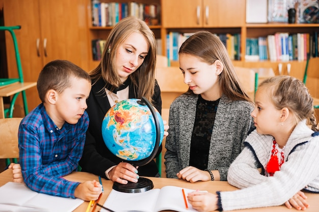 Young woman teaching geography to pupil with globe