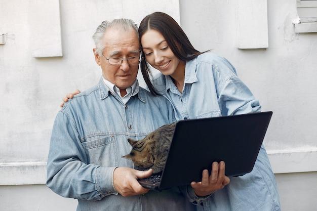 Молодая женщина учит дедушку пользоваться ноутбуком
