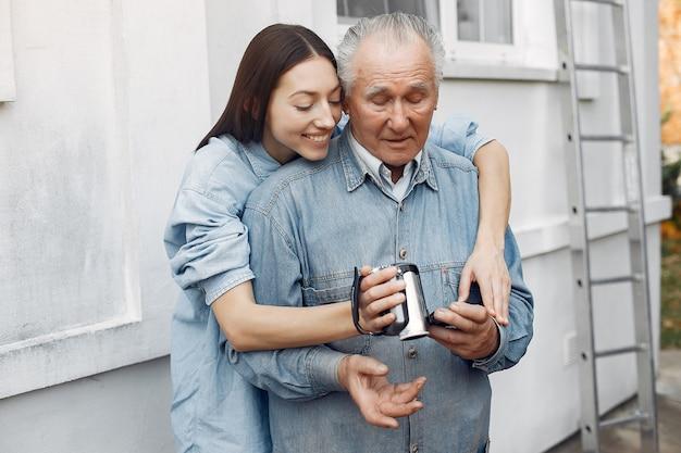 Giovane donna che insegna a suo nonno come usare una macchina fotografica