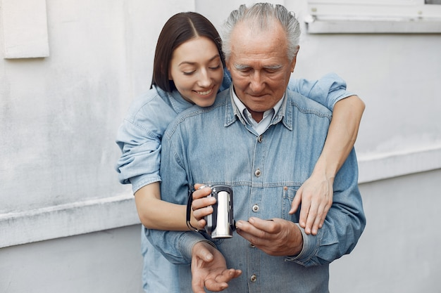 Young woman teaching her grandfather how to use a camera