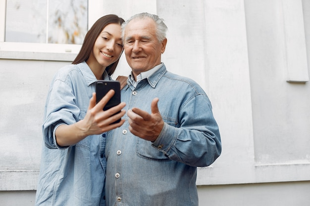 Young woman teaching her grandfather how to use a phone