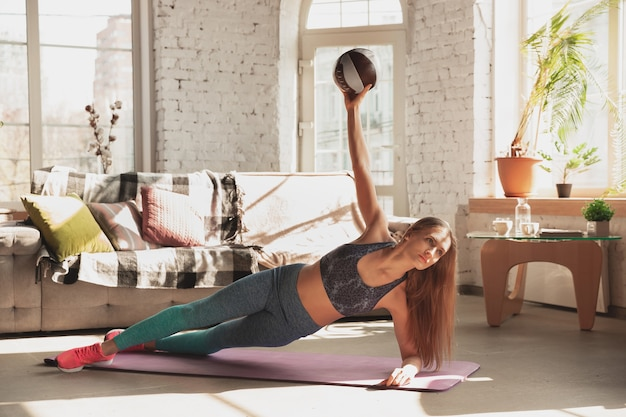 Young woman teaching at home online courses of fitness aerobic sporty lifestyle while being quarantine