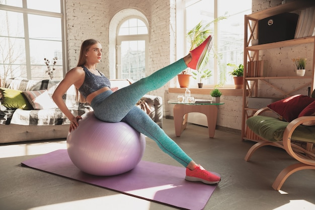 Young woman teaching at home online courses of fitness, aerobic, sporty lifestyle while quarantine. getting active while isolated, wellness, movement concept. exercises with fitball for lower body.
