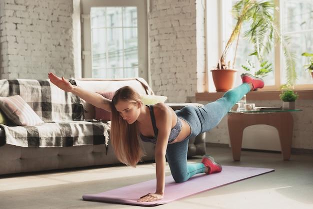 Giovane donna che insegna a casa corsi online di fitness, aerobica, stile di vita sportivo