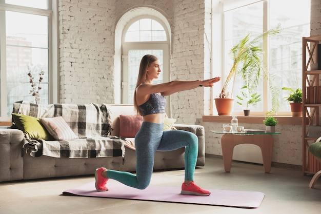 Young woman teaching at home online courses of fitness, aerobic.