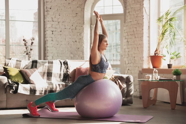 Young woman teaching at home online courses of fitness