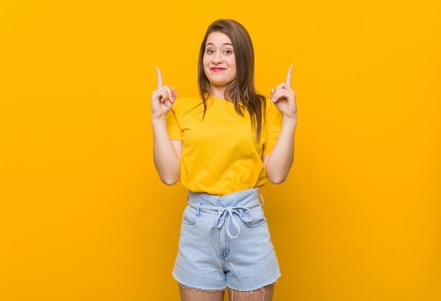 黄色のシャツを着た若い女性10代は、空白のスペースを示す両指で示しています。