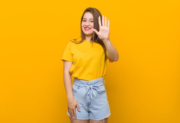 黄色いシャツを着た若い女性のティーンエイジャーは、指で5番を示して陽気に笑っています。