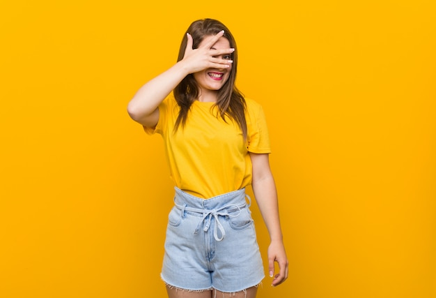 Young woman teenager wearing a yellow shirt blink through fingers, embarrassed covering face.