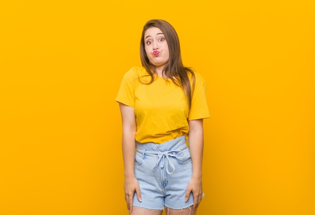 Young woman teenager wearing a yellow shirt blows cheeks, has tired expression. facial expression concept.