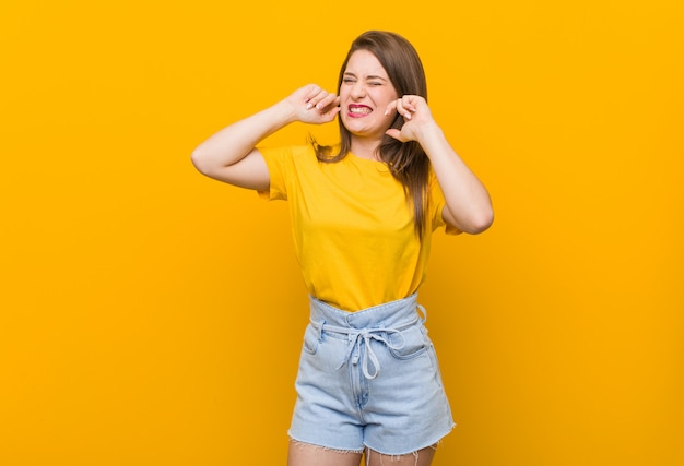 Young woman teenager wearing a yellow shirt covering ears with hands.