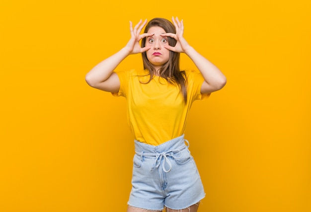 Young woman teenager wearing a yellow shirt keeping eyes opened find a success opportunity.
