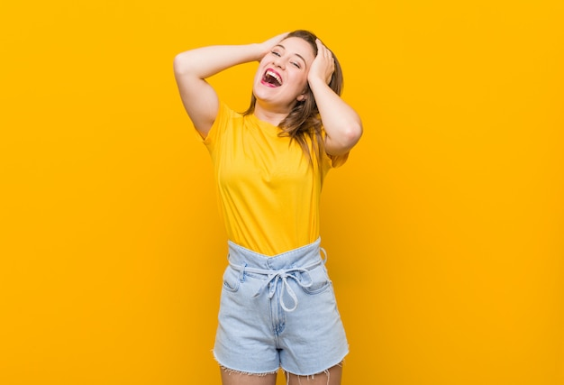 Young woman teenager wearing a yellow shirt laughs joyfully keeping hands on head. happiness concept.