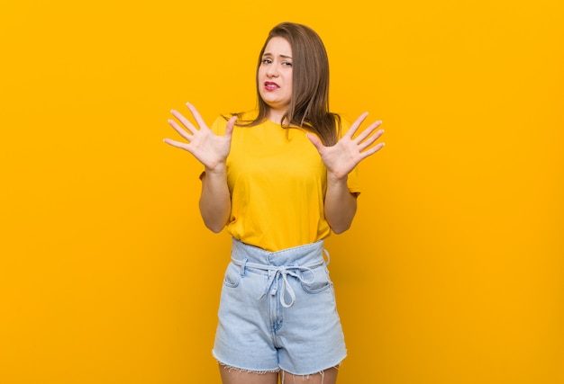 Young woman teenager wearing a yellow shirt rejecting someone showing a gesture of disgust
