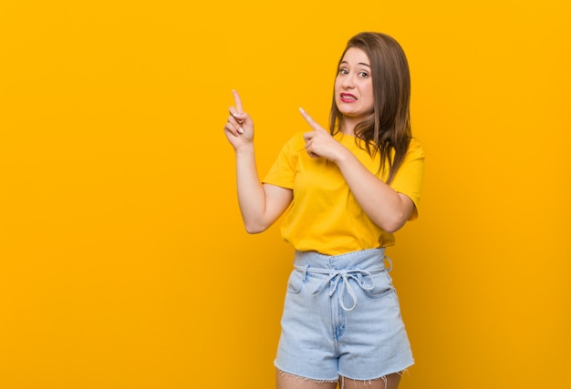 Young woman teenager wearing a yellow shirt shocked pointing with index fingers a copyspace.