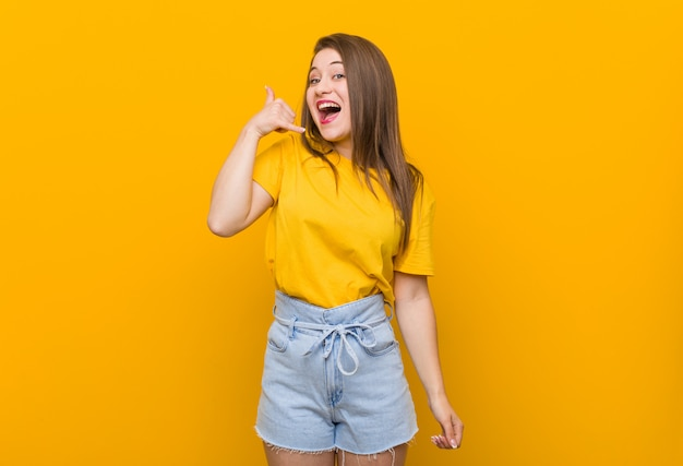 Young woman teenager wearing a yellow shirt showing a mobile phone call gesture with fingers.
